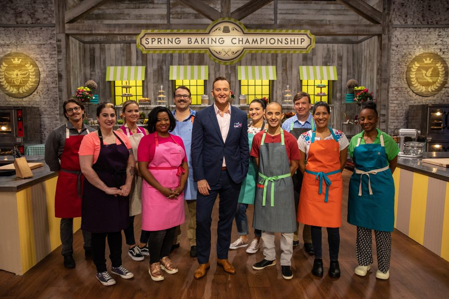 Host Clinton Kelly poses with contestants for a photo, as seen on Spring Baking Championship, Season 5.